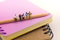 Gente miniatura, sedentesi sulla matita e sul libro colto su un grande libro, usando come istruzione del fondo, o concetto di aff Immagini Stock