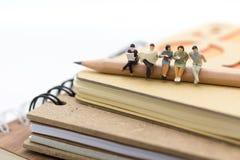 Gente miniatura, sedentesi sulla matita e sul libro colto su un grande libro Uso di immagine per istruzione del fondo, o concetto Immagine Stock