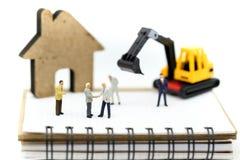 Gente miniatura: sitio de Construction del hombre de negocios con el equipo fotografía de archivo libre de regalías