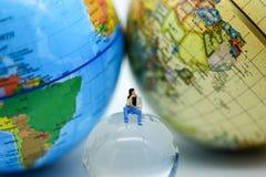 Gente miniatura: Sittng dell'uomo su riscaldamento globale con meteorologia fotografia stock