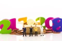 Gente miniatura, soporte del hombre de negocios entre 2017 y 2018 Hay monedas en cajas y monedas en la tierra Imagen de archivo libre de regalías