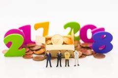 Gente miniatura, soporte del hombre de negocios entre 2017 y 2018 Hay monedas en cajas y monedas en la tierra Imagen de archivo