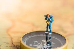 Gente miniatura: Soporte del viajero en el compás para decir la dirección del viaje Uso como concepto del viaje de negocios Foto de archivo libre de regalías