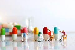 Gente miniatura: Spazzola del gruppo dei lavoratori che dipinge capsula medicinale immagine stock