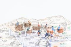 Gente miniatura sulle monete e sulle banconote fotografie stock libere da diritti