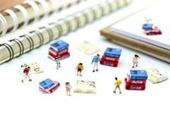 Gente miniatura: supporto con il libro, concetto dei bambini di istruzione Immagini Stock Libere da Diritti