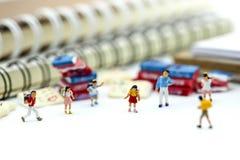 Gente miniatura: supporto con il libro, concetto dei bambini di istruzione Immagine Stock