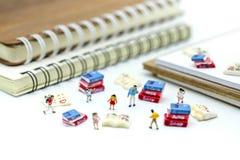 Gente miniatura: supporto con il libro, concetto dei bambini di istruzione Fotografia Stock