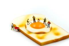 Gente miniatura: trabajador que cocina el huevo de Fried Bread usando para la estafa Fotografía de archivo