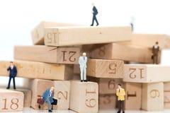 Gente miniatura: Uomini d'affari che stanno in varie posizioni dei numeri di legno, indicanti la sequenza operativa Fotografie Stock