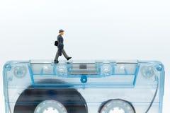 Gente miniatura: Uomo d'affari che cammina sulla cassetta compatta immagine immagine stock libera da diritti
