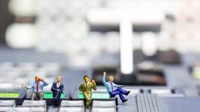 Gente miniatura: uomo d'affari che si siede sul controllo dello scambista di Te Fotografie Stock