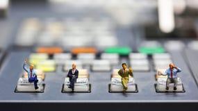 Gente miniatura: uomo d'affari che si siede sul controllo dello scambista di Te Fotografie Stock Libere da Diritti