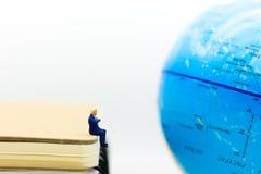 Gente miniatura: Uomo d'affari che si siede sul libro e che guarda per tracciare mondo Concetto di affari di uso di immagine Immagine Stock