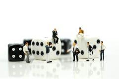 Gente miniatura: uomo d'affari che sta con dic in bianco e nero Fotografia Stock
