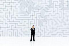 Gente miniatura: Uomo d'affari che sta con un labirinto al fondo Uso di immagine per la soluzione del ritrovamento, concetto di a immagini stock