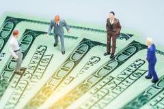 Gente miniatura: Uomo d'affari con le fatture di dollaro americano Immagine Stock Libera da Diritti