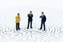 Gente miniatura: Uomo d'affari nel labirinto L'uso di immagine per il rischio, trovante la soluzione per risolve il problema fotografia stock