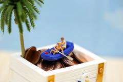 Gente miniatura: Viaggiatori con il cofano o del tesoro del crogiolo di pagaia Immagine Stock
