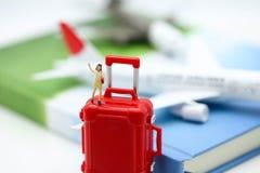 Gente miniatura: viaggiatori con lo zaino che sta sullo sta delle monete Fotografie Stock Libere da Diritti
