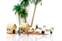 Gente miniatura: Viajeros que se colocan con las casas y los aviones en c imagen de archivo libre de regalías
