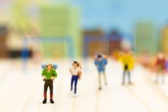 Gente miniatura: Viajeros que se colocan en el fondo blanco, uso de la imagen para el concepto del viaje Fotos de archivo libres de regalías