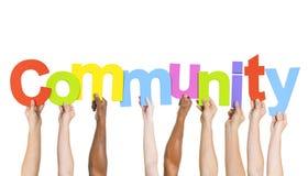 Gente multiétnica que lleva a cabo a la comunidad de la palabra Foto de archivo libre de regalías