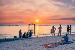 gente Multi-étnica en una playa tropical en la puesta del sol imagen de archivo libre de regalías