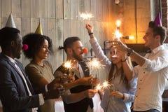 gente Multi-etnica che tengono le stelle filante e vetri che celebrano Ne Immagine Stock