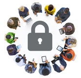 Gente multietnica che per mezzo dei dispositivi di Digital con il simbolo di sicurezza Fotografie Stock Libere da Diritti