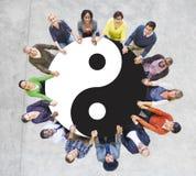 Gente multietnica che si tiene per mano con Yin Yang Symbol Fotografie Stock Libere da Diritti
