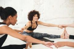 Gente multietnica felice nell'allungamento dello studio di yoga Fotografia Stock Libera da Diritti