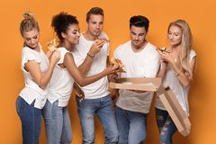 Gente multirracial que se divierte, comiendo la pizza Imagenes de archivo