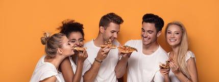 Gente multirracial que se divierte, comiendo la pizza Fotografía de archivo