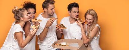 Gente multirracial que se divierte, comiendo la pizza Fotos de archivo