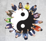 Gente multiétnica que lleva a cabo las manos con Yin Yang Symbol Fotos de archivo libres de regalías