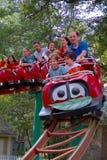 Gente-niños y adultos en una montaña rusa del parque de atracciones Imágenes de archivo libres de regalías