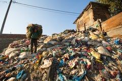 Gente no identificada de áreas más pobres que trabajan en la clasificación del plástico en la descarga Foto de archivo