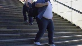 Gente obesa que camina en las escaleras, problema gordo entre la juventud, consumerismo almacen de metraje de vídeo