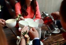 Gente, ocio y concepto de la comunicación - amigos felices que encuentran y que beben té o el café en el café fotos de archivo