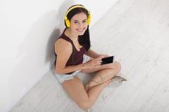 Gente, ocio y concepto de la tecnología - mujer en auriculares, smartphone Fotografía de archivo libre de regalías