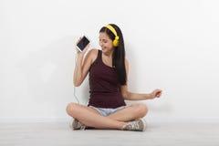Gente, ocio y concepto de la tecnología - mujer en auriculares, smartphone Imágenes de archivo libres de regalías