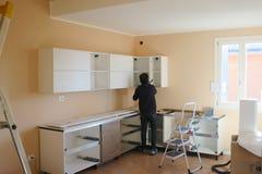 Gente ocupada montando una cocina Foto de archivo libre de regalías