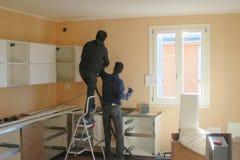 Gente ocupada montando una cocina Imagen de archivo libre de regalías