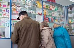Gente più anziana nelle finestre della farmacia Immagini Stock Libere da Diritti