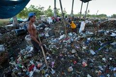 Gente pobre que trabaja en un barrido en el vaciado Foto de archivo libre de regalías