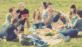 Gente positiva que se sienta en comida campestre junto Imágenes de archivo libres de regalías