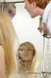 Gente que admira la cara en espejo Imagen de archivo