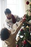 Gente que adorna el árbol de navidad Imagen de archivo libre de regalías