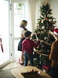 Gente que adorna el árbol de navidad Fotos de archivo